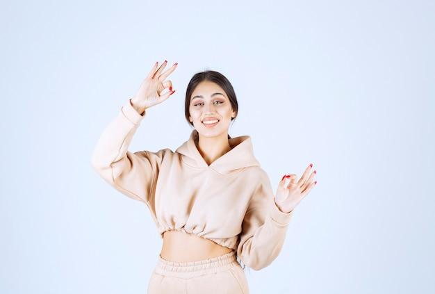 Młoda kobieta w różowej bluzie z kapturem pokazuje znak ręki satysfakcji