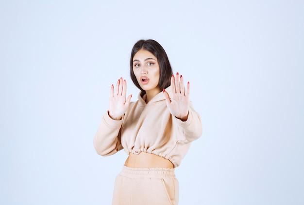 Młoda kobieta w różowej bluzie z kapturem powstrzymuje niepożądaną rzecz