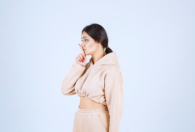 Młoda kobieta w różowej bluzie z kapturem prosi o ciszę