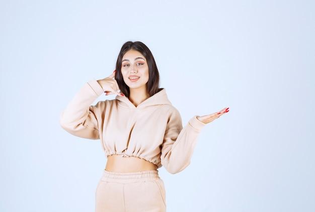 Młoda kobieta w różowej bluzie z kapturem prosi o telefon