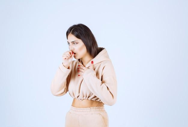Młoda kobieta w różowej bluzie z kapturem śmieje się i ma ból gardła