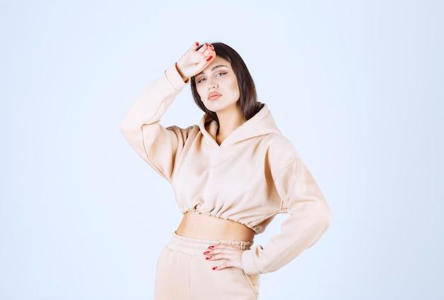 Młoda kobieta w różowej bluzie z kapturem, trzymając głowę, ponieważ ma ból głowy