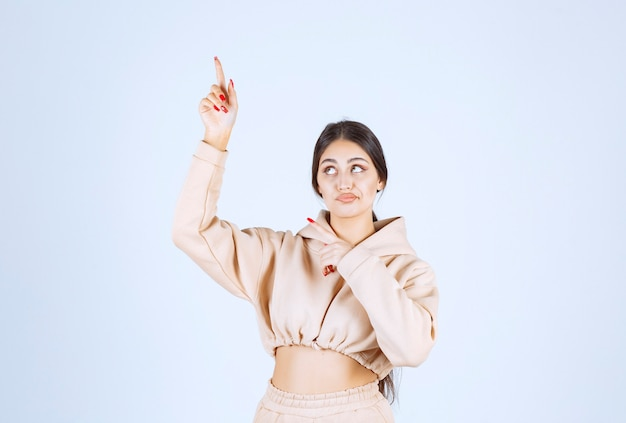 Młoda kobieta w różowej bluzie z kapturem wskazująca gdzieś powyżej