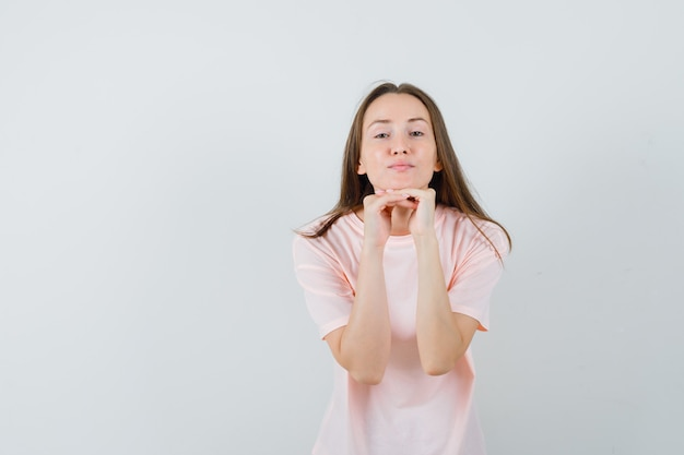Młoda kobieta w różowej koszulce podpierając brodę na rękach i ładnie wyglądający widok z przodu.