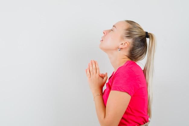Młoda kobieta w różowej koszulce, trzymając się za ręce w geście modlitwy i patrząc z nadzieją