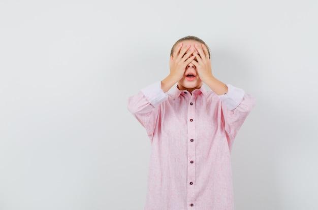 Młoda kobieta w różowej koszuli obejmujące oczy rękami i patrząc podekscytowany