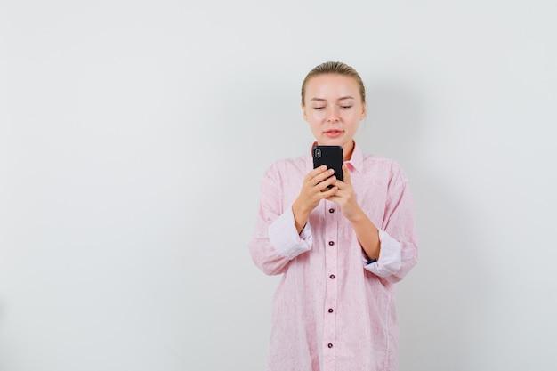 Młoda kobieta w różowej koszuli przy użyciu telefonu komórkowego i patrząc zajęty