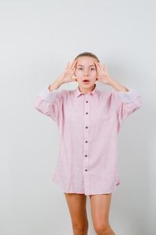 Młoda kobieta w różowej koszuli, trzymając się za ręce, aby zobaczyć wyraźnie i ciekawie