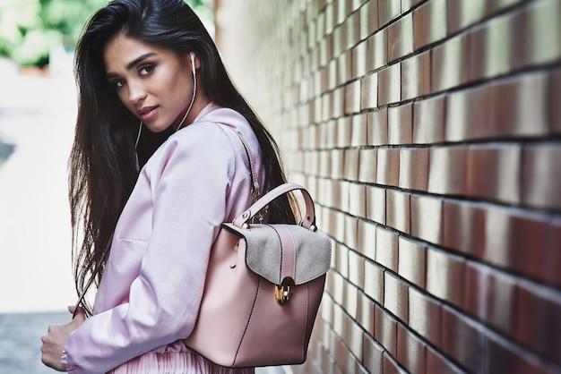 Młoda kobieta w różowej kurtce niosąca plecak idący w pobliżu ściany l