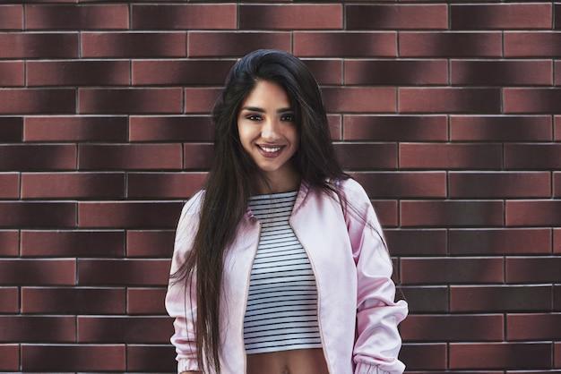Młoda kobieta w różowej kurtce, odizolowana na ścianie, patrząc przyszła