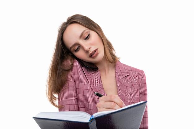 Młoda kobieta w różowej kurtce pisze w pamiętniku i jednocześnie rozmawia przez telefon