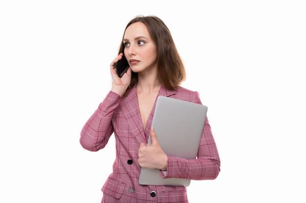 Młoda kobieta w różowej kurtce rozmawia przez telefon i trzyma laptopa