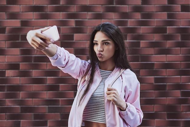 Młoda kobieta w różowej kurtce stojąca odizolowana na ścianie biorąca siebie