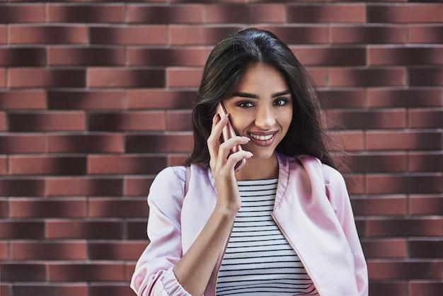 Młoda kobieta w różowej kurtce stojąca odizolowana na ścianie rozmawiająca z dowcipem