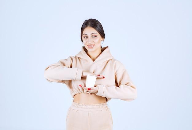 Młoda kobieta w różowej piżamie trzymając kubek napoju