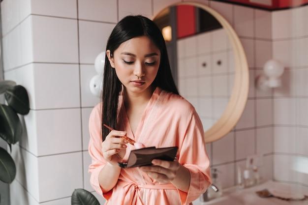 Młoda kobieta w różowej szacie robi makijaż