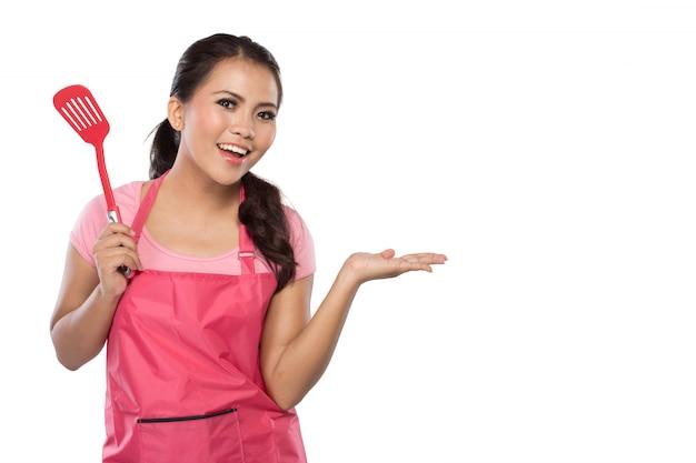 Młoda kobieta w różowym fartuchu z łopatką