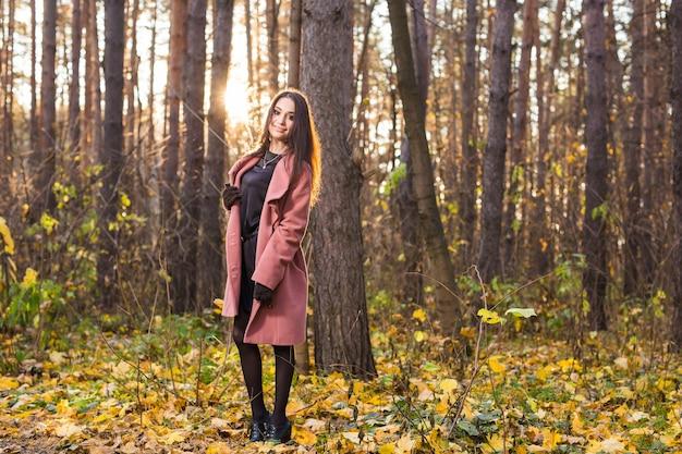 Młoda kobieta w różowym płaszczu na tle przyrody jesień