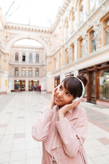 Młoda kobieta w różowym płaszczu słuchanie muzyki w słuchawkach poza