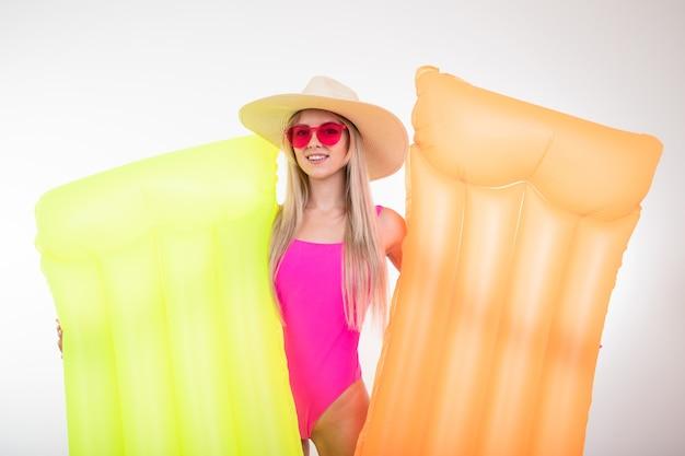 Młoda kobieta w różowym stroju kąpielowym i kapeluszu trzyma dwa dmuchane materace