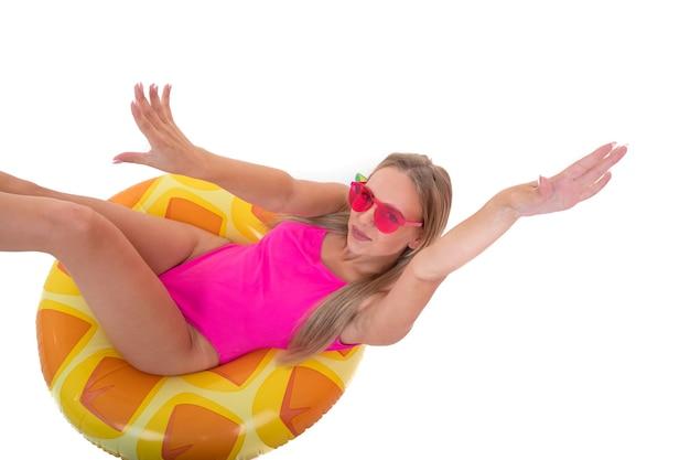 Młoda kobieta w różowym stroju kąpielowym leży na nadmuchiwanym kółku do pływania