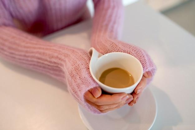 Młoda kobieta w różowym swetrze trzyma filiżankę kawy, zbliżenie