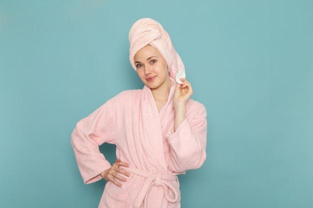 Młoda kobieta w różowym szlafroku po prysznic ładny pozowanie na niebiesko