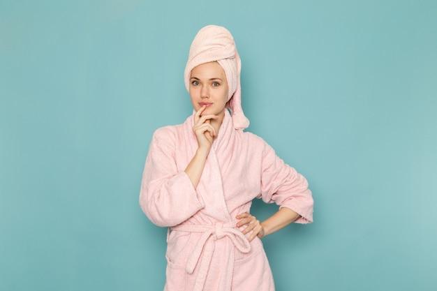 Młoda kobieta w różowym szlafroku po prysznicu pozowanie na niebiesko