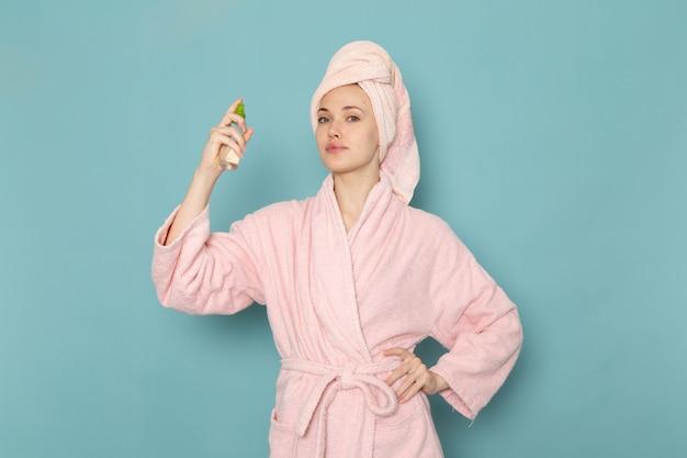 Młoda kobieta w różowym szlafroku po prysznicu przy użyciu sprayu na niebiesko
