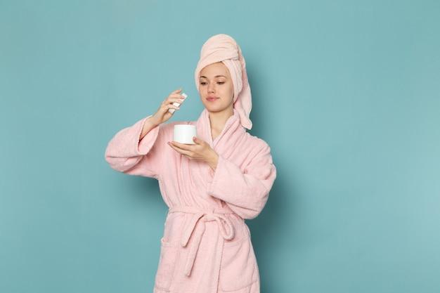 Młoda kobieta w różowym szlafroku po prysznicu, trzymając i używając kremu na niebiesko