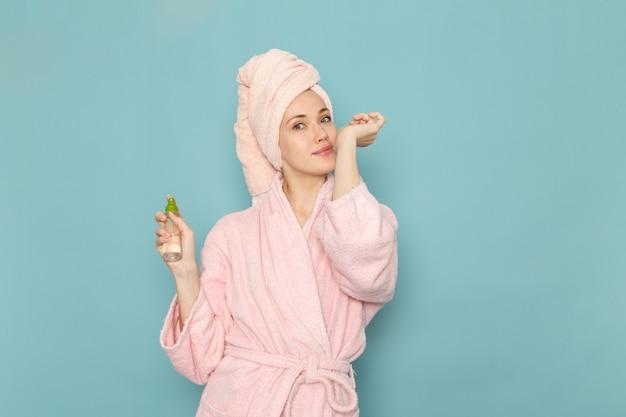 Młoda kobieta w różowym szlafroku po prysznicu, trzymając i używając sprayu na niebiesko