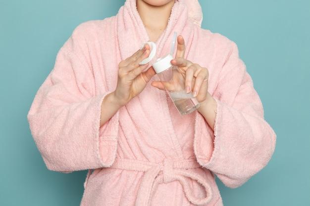 Młoda kobieta w różowym szlafroku przy użyciu środka do czyszczenia makijażu na niebiesko