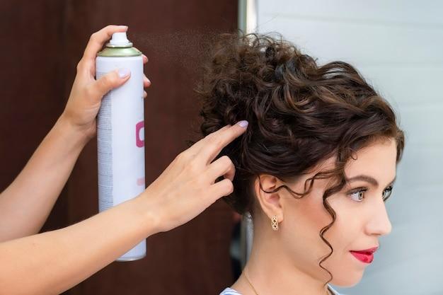Młoda kobieta w salonie piękności. fryzjer wykonuje fryzurę. lakier do włosów.
