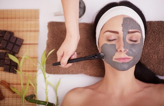 Młoda kobieta w salonie piękności mająca maskę na twarz