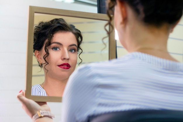 Młoda kobieta w salonie piękności, patrząc w lustro