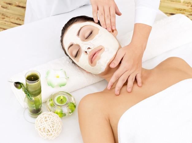 Młoda kobieta w salonie spa z kosmetyczną maską na twarzy. zdjęcie pod dużym kątem