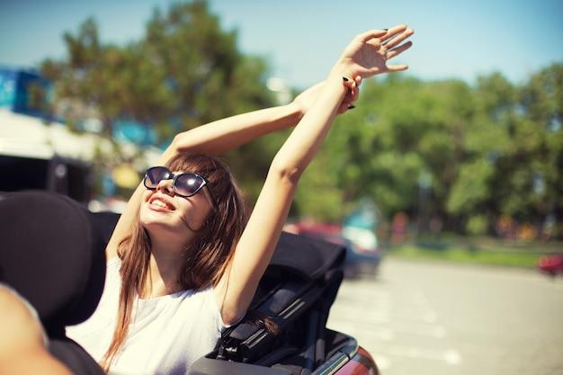 Młoda kobieta w samochodzie kabriolet wyjeżdża na wakacje