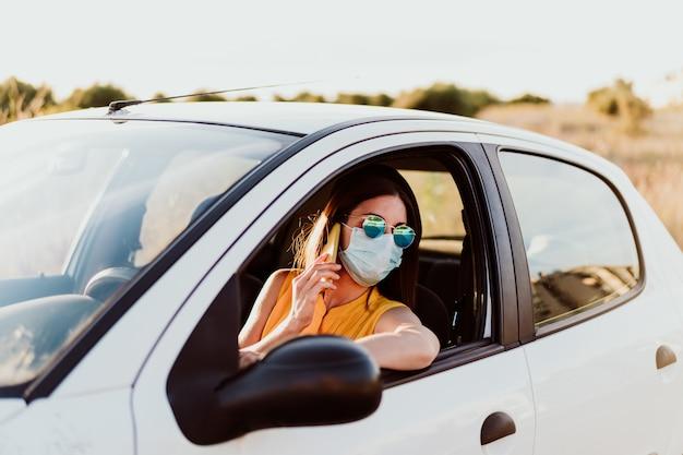 Młoda kobieta w samochodzie przy użyciu telefonu komórkowego, noszenie maski ochronnej