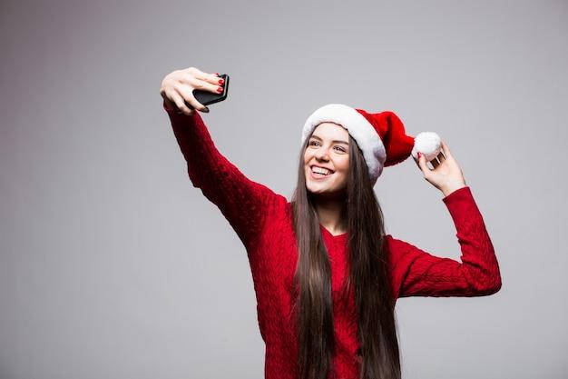 Młoda kobieta w santa hat bierze selfie na telefon na białym tle na szarej ścianie