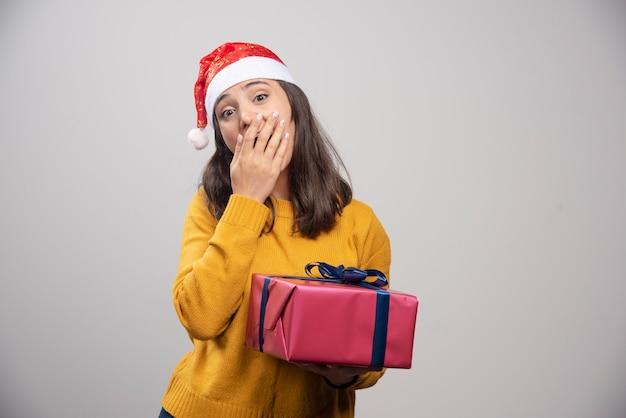 Młoda kobieta w santa hat gospodarstwa pudełko.