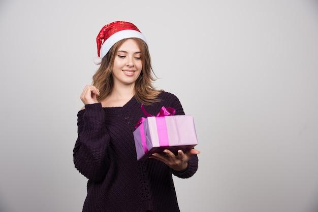 Młoda kobieta w santa hat patrząc na prezent pudełko.