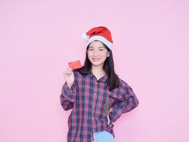 Młoda kobieta w santa hat trzyma kartę kredytową na różowej ścianie.