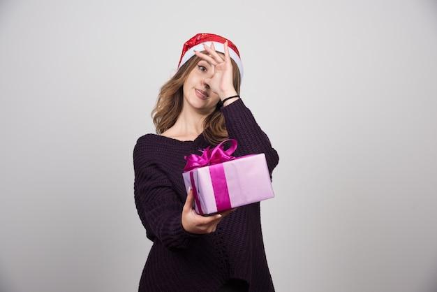 Młoda kobieta w santa hat trzyma prezent pudełko.