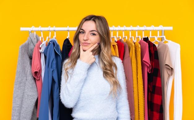 Młoda kobieta w sklepie odzieżowym nad odosobnioną kolor żółty ścianą myśleć pomysł