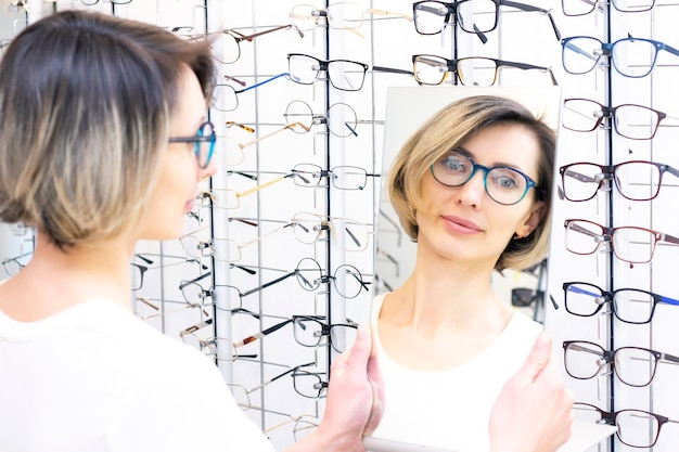 Młoda kobieta w sklepie optycznym wybiera nowe okulary z optykiem. okulary w sklepie optycznym. kobieta wybiera okulary. emocje. okulistyka.
