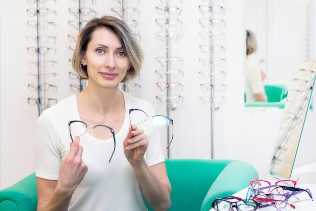 Młoda kobieta w sklepie optycznym wybiera nowe okulary z optykiem. okulary w sklepie optycznym. kobieta wybiera okulary. wiele szklanek w ręku. okulistyka.