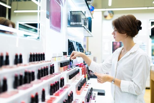Młoda kobieta w sklepie z kosmetykami wybiera lakier do paznokci