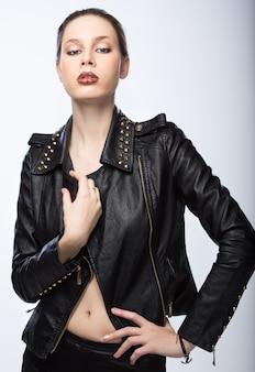 Młoda kobieta w skórzanej kurtce na szarym tle
