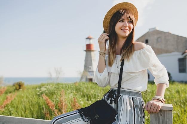 Młoda kobieta w słomianym kapeluszu na wsi