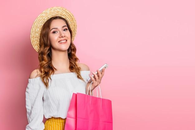 Młoda kobieta w słomkowym kapeluszu i białej letniej sukience z telefonem komórkowym i torbami na zakupy uśmiecha się na różowej ścianie na baner tekstowy. dziewczyna robi zakupy online w studio